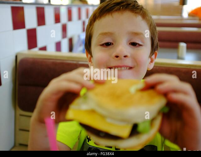 Close-Up Of Boy Holding Burger In Restaurant - Stock Image