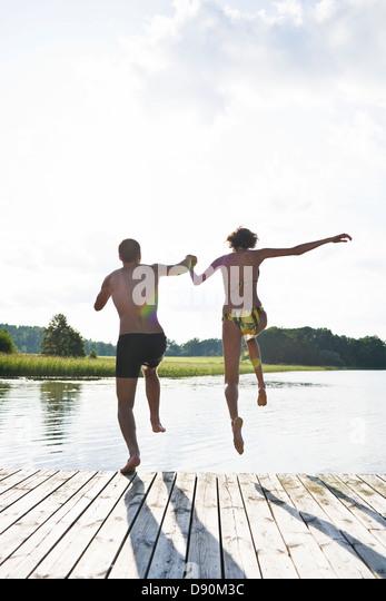 Couple jumping into lake - Stock-Bilder