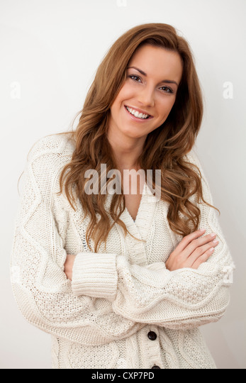 Beautiful woman standing and smiling wearing a big warm baggy jumper / cardigan with her arms folded - Stock Image