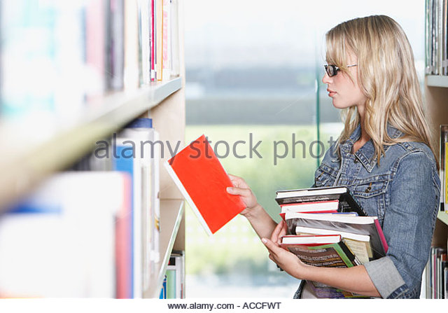 Young Woman in library at school with books - Stock Image