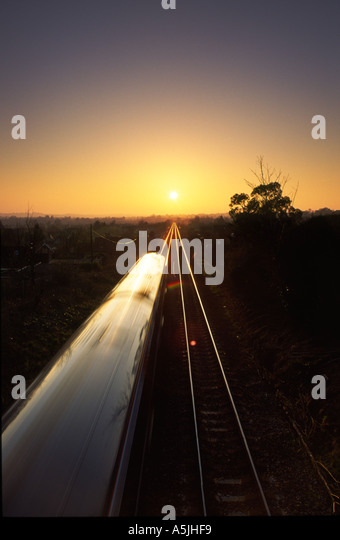 Train driving directly towards the setting sun on the distant horizon in Bradford Abbas village Dorset county England - Stock Image