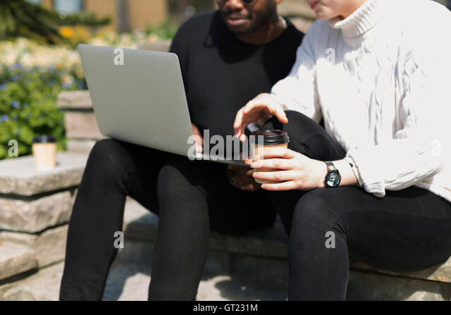 Midsection of man using laptop while woman holding coffee cup on steps - Stock-Bilder