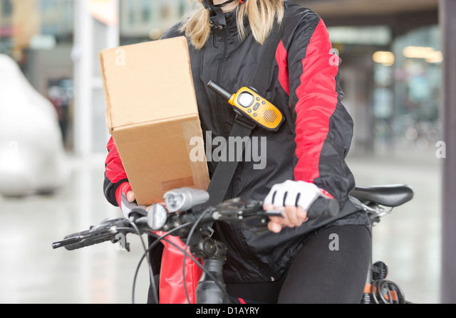 Female Cyclist With Cardboard Box And Courier Bag On Street - Stock-Bilder