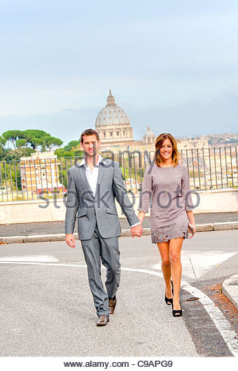 Couple walking in front of Saint Peter's dome - Stock Image