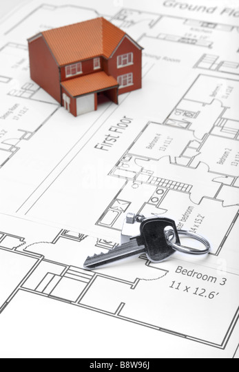 A model home and house key on architectural floor plans - Stock Image