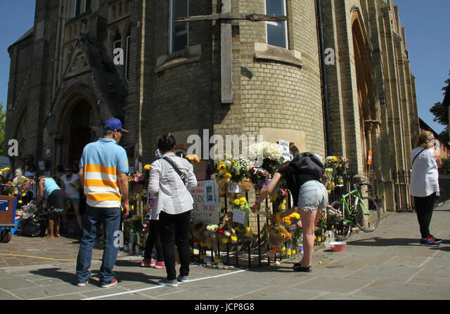 London, UK. 16th June, 2017. People seen reading through memorial messages places outside the Notting Hill Methodist - Stock Image