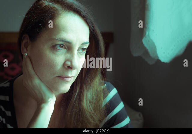 Portrait of a woman looking to a window and with a hand on her neck thinking with doubts, uncertain future - Stock Image