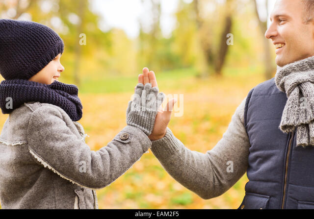 happy father and son making high five in park - Stock Image