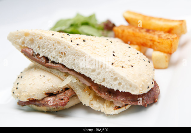 Steak and onion sandwich served as bar food, with salad and chips - Stock Image