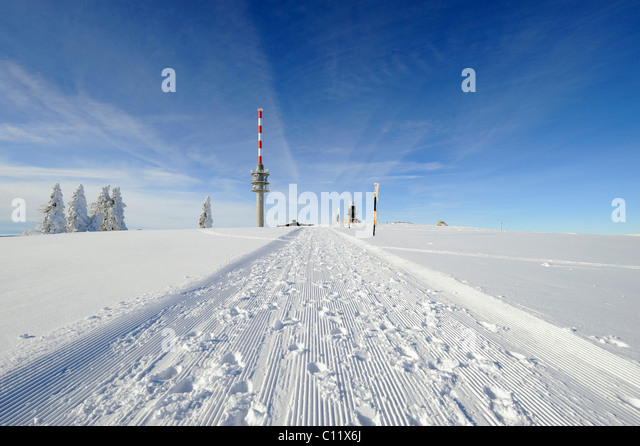 Rolled snow trail on the 1493m high Mt. Feldberg in the Black Forest, on the horizon the new Feldbergturm antenna - Stock Image