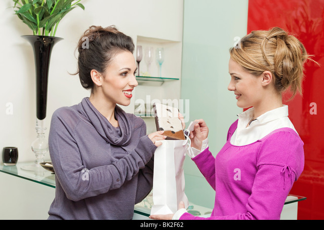 A woman buying a purse in a shop - Stock Image