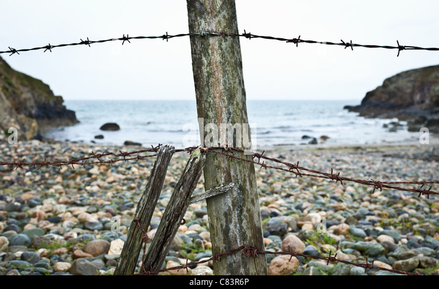 Barbed wire fence on rocky beach - Stock Image
