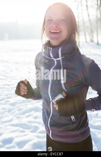 Young woman with MP3 player in snow - Stock Image