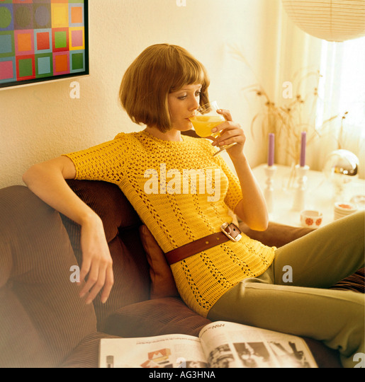 people, women, 1960s, woman sitting on a cord sofa and drinking orange juice, half length, fashion, 60s, historic, - Stock Image