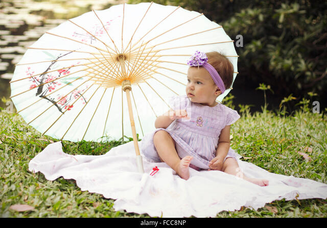 Full Length Of A Pretty Baby Girl Sitting With Umbrella On Grassland - Stock Image