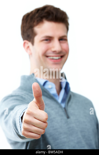 Handsome man showing thumb up and smiling - Stock Image