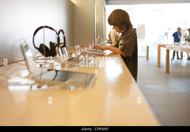 Nine year old boy tries out the latest version of ipad tablet at an Apple store. - Stock Image