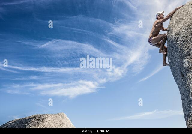 Man wearing swimming trunks climbing rock, Villasimius, Sardinia, Italy - Stock Image