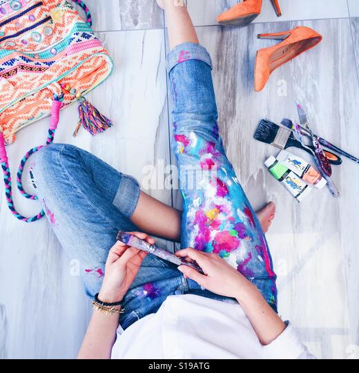 Artist relaxing wearing paint covered blue jeans with painting accessories and brightly covered bag and heels. - Stock Image
