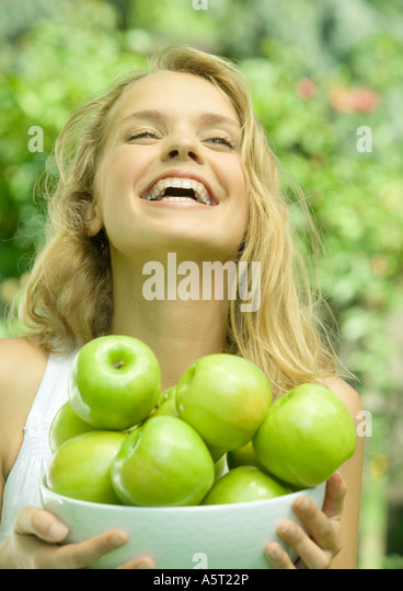Woman holding bowl of apples, laughing - Stock Image