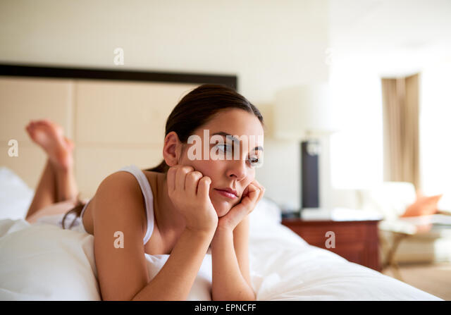 Attractive woman lying in bed resting chin in hands looking sad. - Stock Image