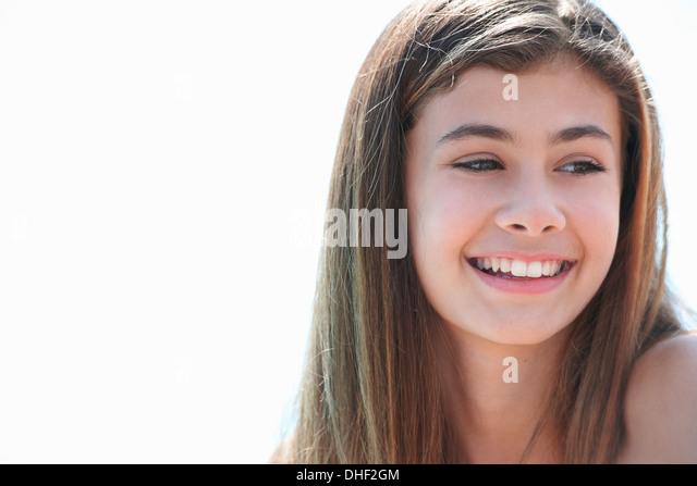 Portrait of brunette teenage girl looking away, smiling - Stock-Bilder