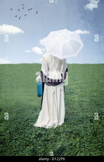 a woman with a parasol and a suitcase on a meadow - Stock Image