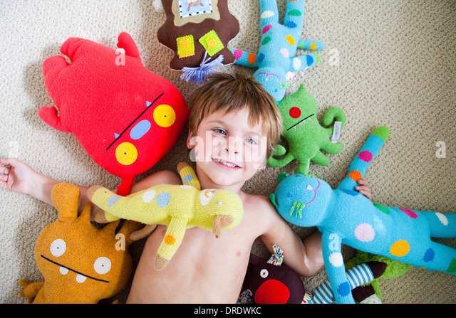 Young boy covered in stuffed toys - Stock-Bilder