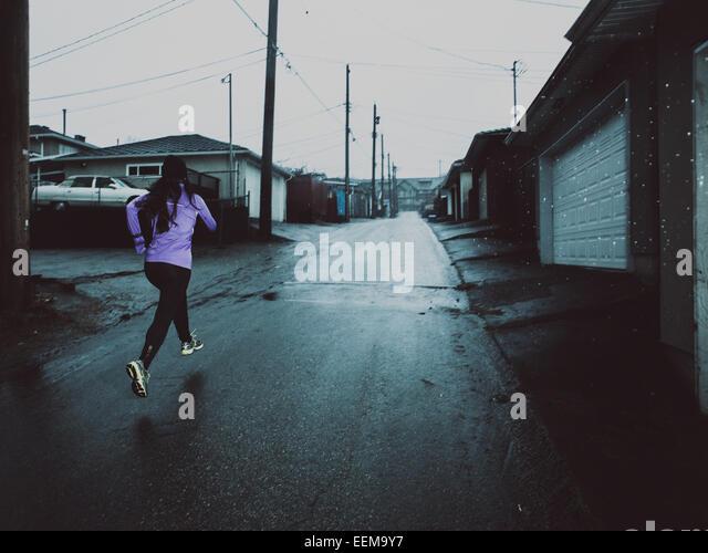 Young woman running along street at dusk - Stock-Bilder