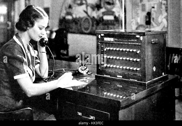 A female switchboard operator speaks into a headset while operating a small telephone branch exchange switchboard, - Stock Image