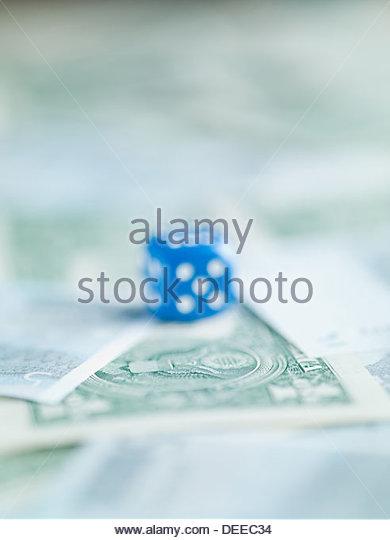 Blur blue dice on pile of dollar bills - Stock Image