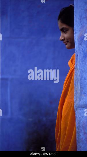 Young women wearing orange Sari stands between blue walls Jodhpur Rajasthan India - Stock Image