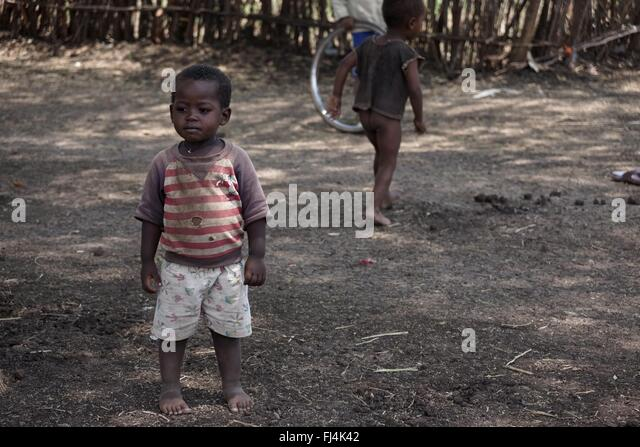 A young boy stares out at the passing people - Stock-Bilder