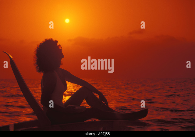 Tropical Beach Silhouette Woman on lounge chair looking at the sun orange sky dramatic - Stock Image
