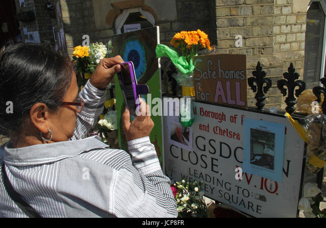 London, UK. 16th June, 2017. A woman snaps at a memorial sign outside the Notting Hill Methodist Church. At least - Stock Image