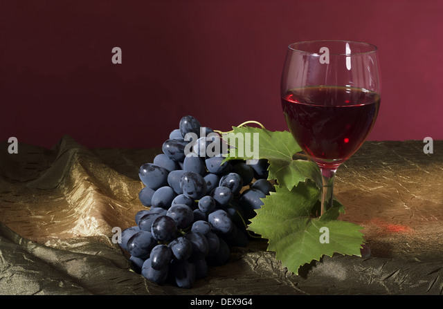 Still life with clusters of dark grapes and wine - Stock Image