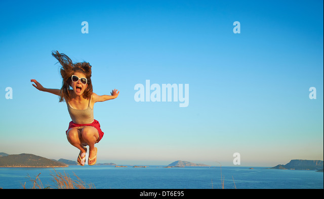 Energetic girl jumping mid air, Kas, Turkey - Stock Image