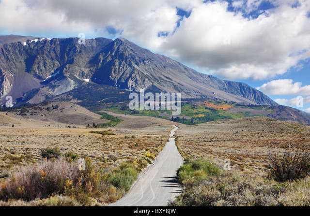 The narrow asphalt road in the picturesque blooming steppe to the distant mountains - Stock-Bilder