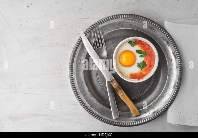 Eggs baked with tomatoes and parsley in the ramekins with cutlery top view - Stock Image