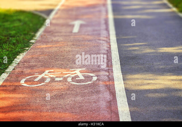Red bike lane on sidewalk with painted white bicycle and arrow signs. Copy space - Stock Image