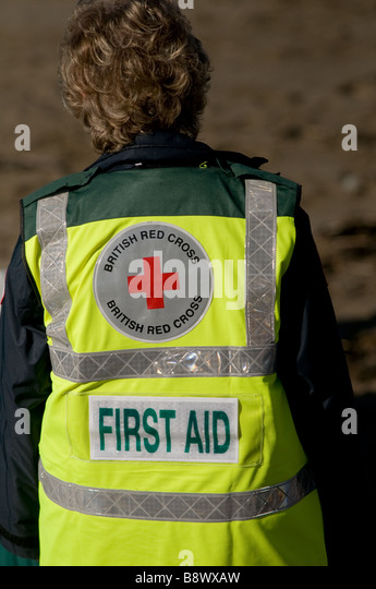 First aid volunteer British Red Cross worker wearing a yellow high visibility jacket coat UK - Stock Image