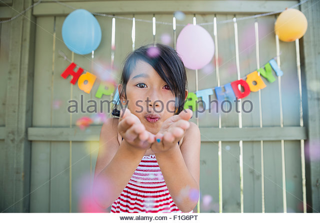 Portrait girl blowing confetti at birthday party - Stock Image