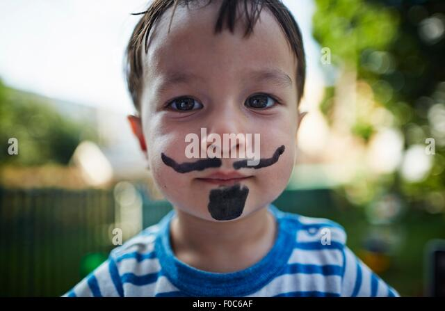 Close up portrait of boy looking at camera wearing beard and moustache face paint costume - Stock-Bilder