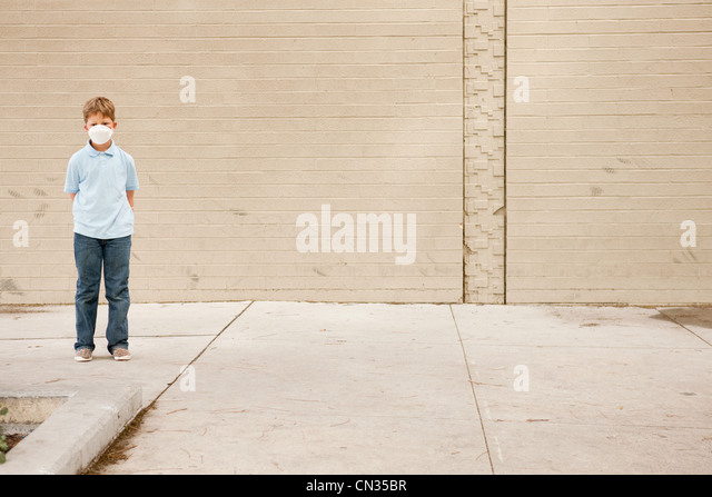 Young boy standing by brick wall wearing dust mask - Stock Image
