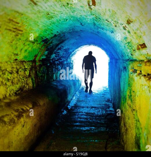 Anonymous silhouette of a person walking through a dark underpass symbolizing light at the end of the tunnel - Stock-Bilder