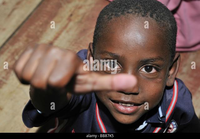 Dark-skinned boy giving an ok sign with his thumb, slums of Alto de Cazuca, Soacha, Bogotá, Columbia - Stock Image