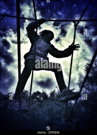 Girl on rope climbing frame - Stock Image