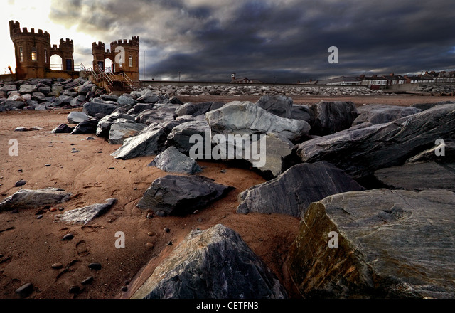 A view from beside the rocks on the beach to the Old Pier Towers at Withernsea. - Stock Image