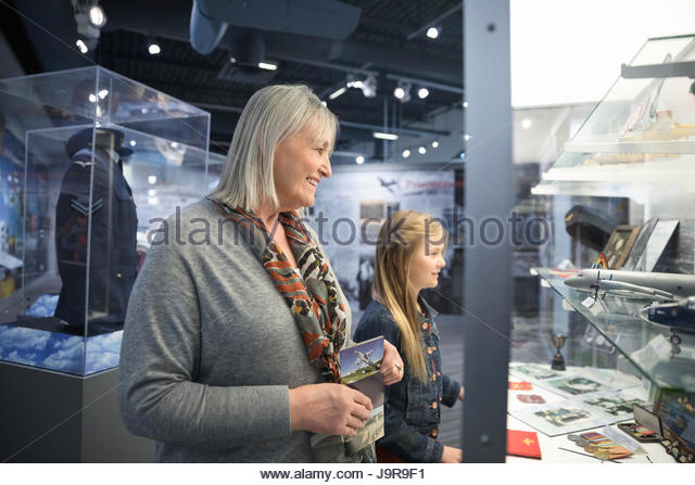 Grandmother and granddaughter looking at exhibit artifacts in war museum - Stock-Bilder