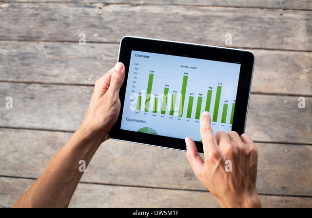 tablet with green chart in hands of business man - Stock-Bilder